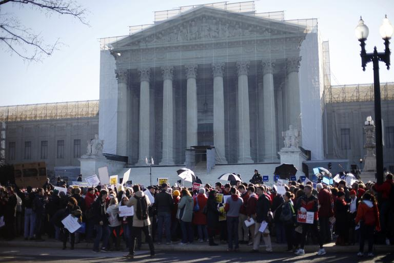 Demonstrators stand outside the Supreme Court in Washington, Tuesday, March 26, 2013, where the court will hear arguments on California's voter approved ban on same-sex marriage, Proposition 8. (Pablo Martinez Monsivais/AP)