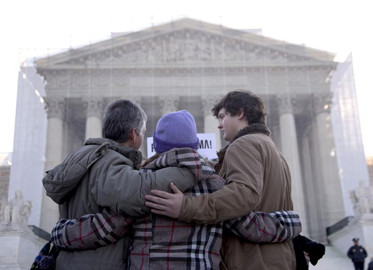 A group from Alabama prays in front of the Supreme Court in Washington, Wednesday, March 27, 2013, before the court's hearing on the Defense of Marriage Act (DOMA). (AP/Carolyn Kaster)