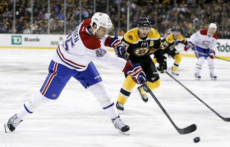 Montreal Canadiens' Michael Blunden (45) takes a shot in front of Bruins' Patrice Bergeron (37). (Michael Dwyer/AP)