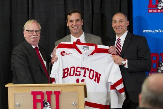 President Robert A. Brown (left) and Mike Lynch, assistant VP and director of athletics, present a jersey to newly appointed men's hockey head coach David Quinn. (Cydney Scott/BU)