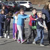 In this photo provided by the Newtown Bee, Connecticut State Police lead children from the Sandy Hook Elementary School in Newtown, Conn., following a reported shooting there Friday, Dec. 14, 2012.  (Newtown Bee, Shannon Hicks/AP)