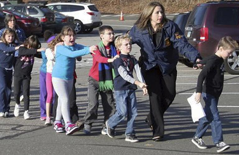 In this photo provided by the Newtown Bee, Connecticut State Police lead children from the Sandy Hook Elementary School in Newtown, Conn., following a reported shooting there Friday, Dec. 14, 2012. (Shannon Hicks/Newtown Bee, AP)