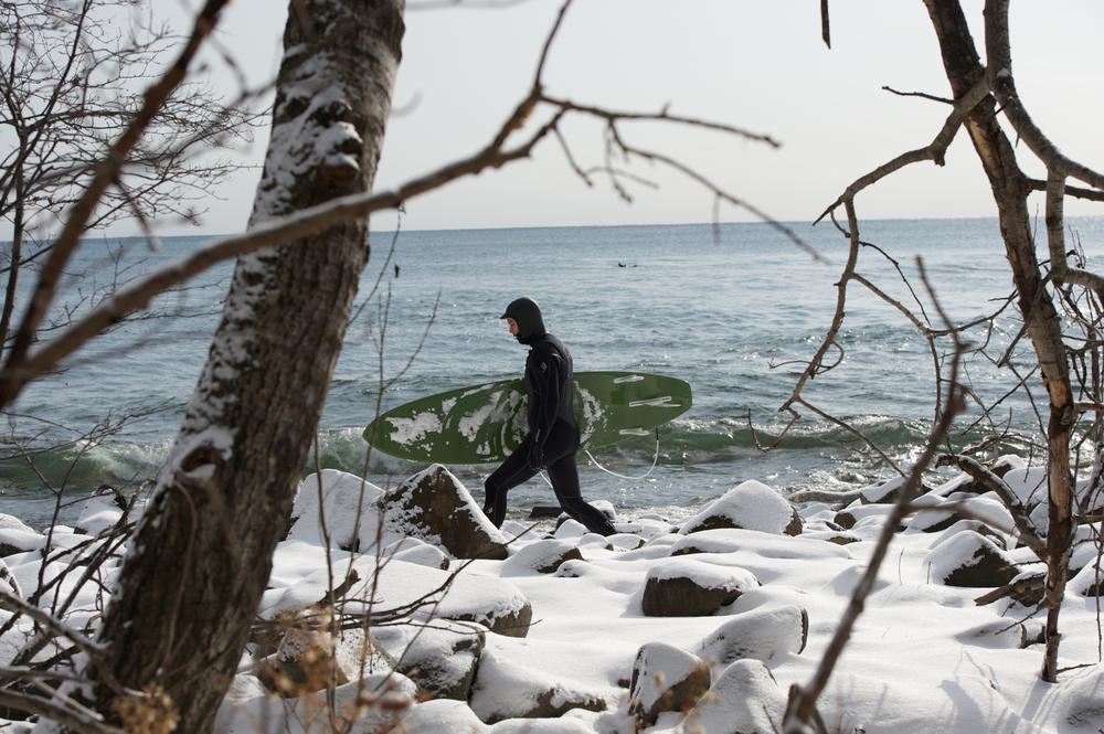 A surfer strides over ice covered rocks to reach the winter surf on Lake Superior. (Bob Tema)