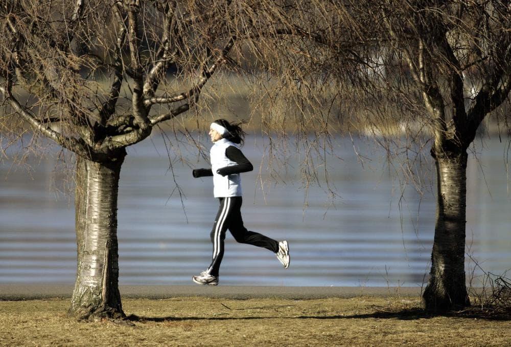 A woman jogs along a partially-frozen Charles River in Boston. (AP Photo/Michael Dwyer)