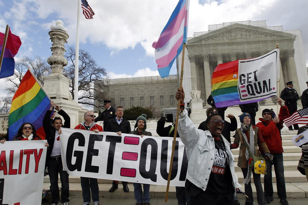 In this photo taken Wednesday, March 27, 2013, demonstrators holding flags chants in front of the Supreme Court in Washington. The U.S. Supreme Court, in the second day of gay marriage cases, turned Wednesday to a constitutional challenge to the federal law that prevents legally married gay Americans from collecting federal benefits generally available to straight married couples. (AP Photo/. (AP Photo/Jose Luis Magana)