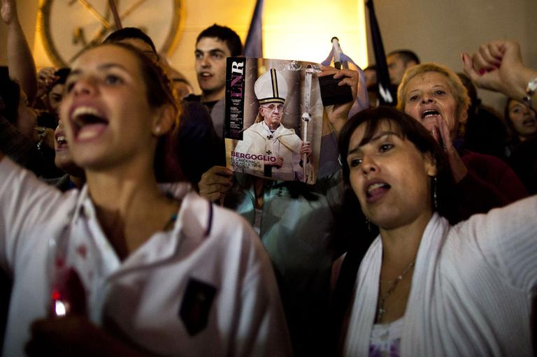 A worshiper holds up the front page of a magazine showing a photograph of Jorge Mario Bergoglio during celebrations outside the Metropolitan Cathedral in Buenos Aires, Argentina, Wednesday, March 13, 2013. (AP)