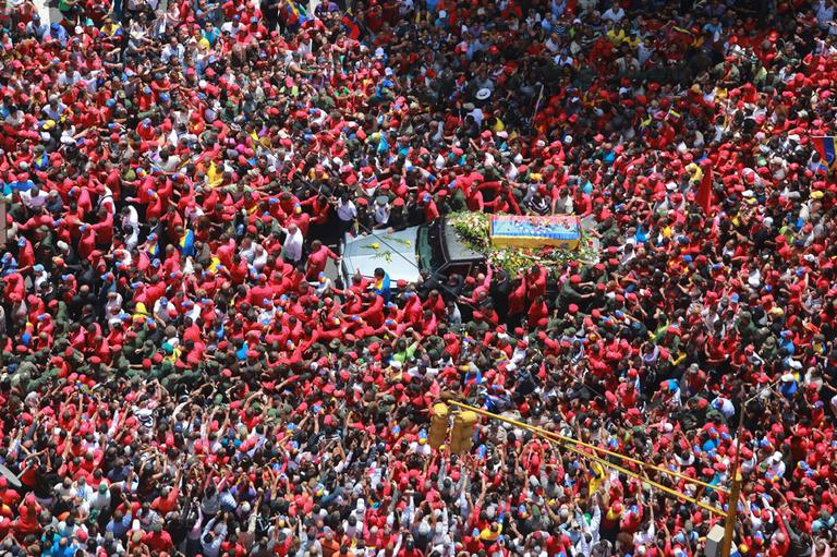 In this photo released by Miraflores Press Office, people surround the flag-draped coffin carrying the body of Venezuela's late President Hugo Chavez as his supporters crowd the streets during the procession from the hospital where he died on Tuesday to a military academy where his body will lie in state in Caracas, Venezuela, Wednesday, March 6, 2013. (AP)