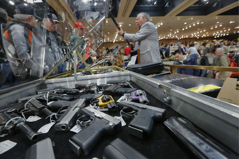 Handguns on display at the table of David Petronis of Mechanicville, N.Y., right, who owns a gun store there, during the heavily attended annual New York State Arms Collectors Association Albany Gun Show at the Empire State Plaza Convention Center, on Saturday, Jan. 26, 2013, in Albany, N.Y. (AP)