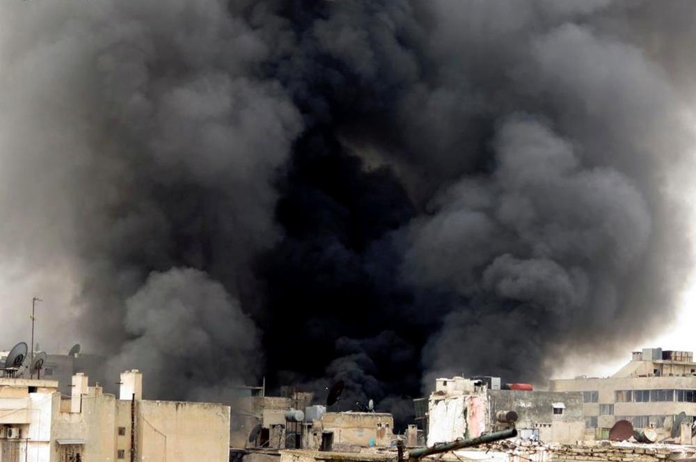 In this Tuesday March 19, 2013, citizen journalism image provided by Aleppo Media Center AMC which has been authenticated based on its contents and other AP reporting, black smoke rise from buildings due to government forces shelling, in Aleppo, Syria. (AP)