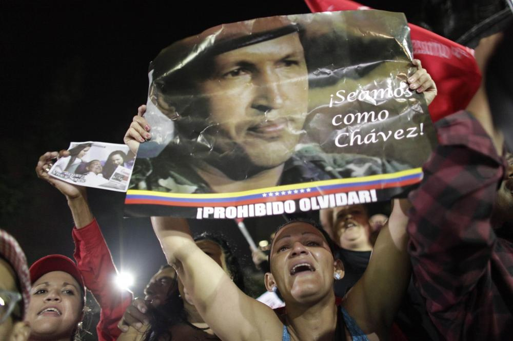"""A supporter of Venezuela's late President Hugo Chavez cries as she holds up a poster of Chavez that reads in Spanish """"Let's be like Chavez"""" and """"Forbidden to forget"""" as Chavistas gather in Bolivar square to mourn Chavez's death in Caracas, Venezuela, Tuesday, March 5, 2013. (AP)"""