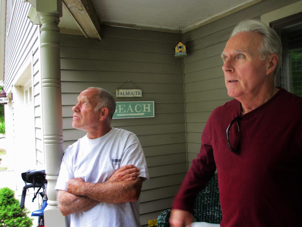 Neil Andersen and John Ford stand on the back porch of Andersen's house on Blacksmith Shop Road in Falmouth. Both say the town's wind turbines have caused them health issues. (Kathleen McNerney/WBUR)