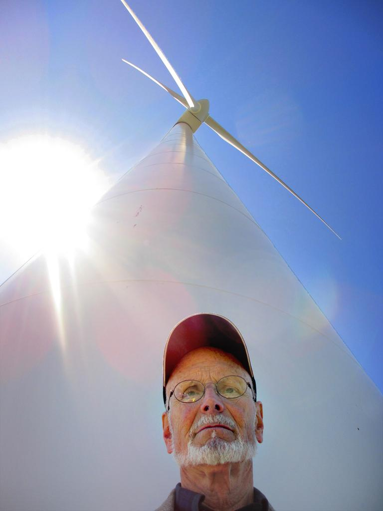Last year, Malcolm Brown stands under the turbine he helped usher through in Hull. There have been very few complaints about the two turbines in Hull. (Kathleen McNerney/WBUR)