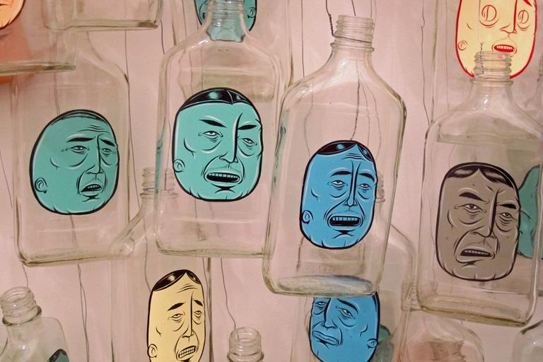 McGee paid homeless men for their empty bottles and then painted these faces on them. (Andrea Shea/WBUR)