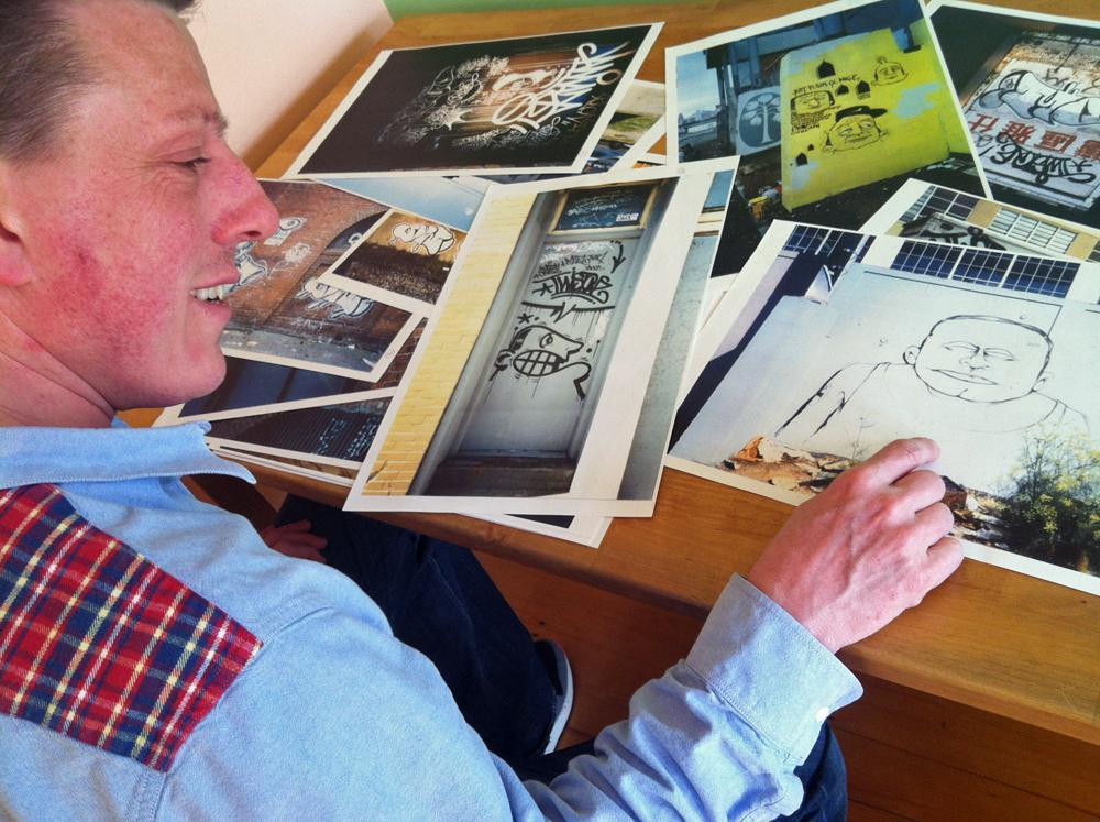 """Caleb Neelon is a public artist and author of """"The History Of American Graffiti."""" Here he is with his trove of pictures of Barry McGee's work from the 1980s and 1990s. (Andrea Shea/WBUR)"""