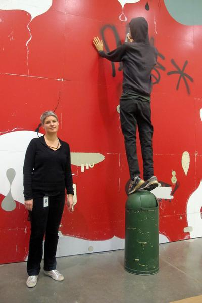 ICA senior curator Jenelle Porter stands next to a grafitti writer sculpture that is part of McGee's installation. (Andrea Shea/WBUR)