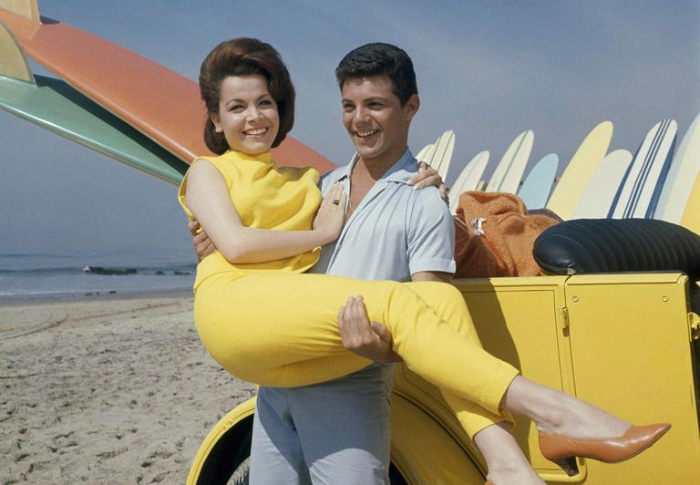 """In this 1963 photo, singer Frankie Avalon and actress Annette Funicello are seen on Malibu Beach during filming of """"Beach Party,"""" in California in 1963. (AP)"""