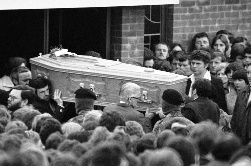 Escorted by masked IRA men, the coffin containing the body of hunger striker Bobby Sands leaves a church near his home in the Twinbrooks area of Belfast, Northern Ireland on May 7, 1981, en route to the city's Milltown cemetery. Sands died after 66 days on hunger strike. (Peter Kemp/AP)