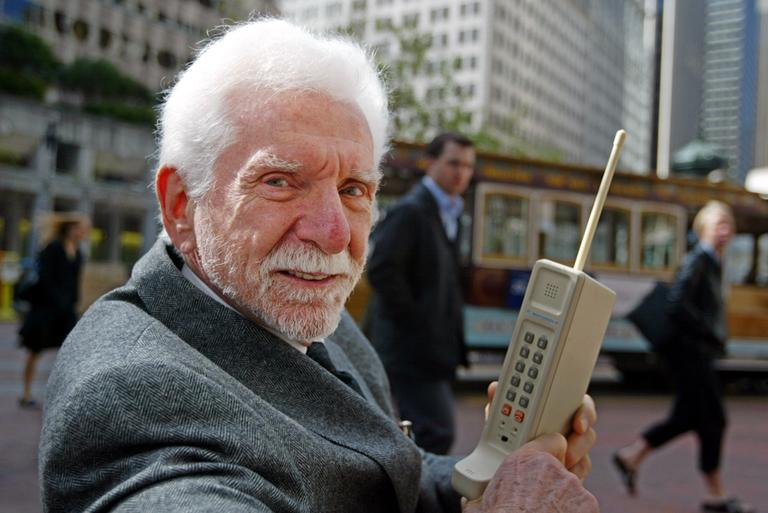 Martin Cooper, chairman and CEO of ArrayComm, is pictured in 2003 holding a Motorola DynaTAC, a 1973 prototype of the first handheld cellular telephone. (Eric Risberg/AP)