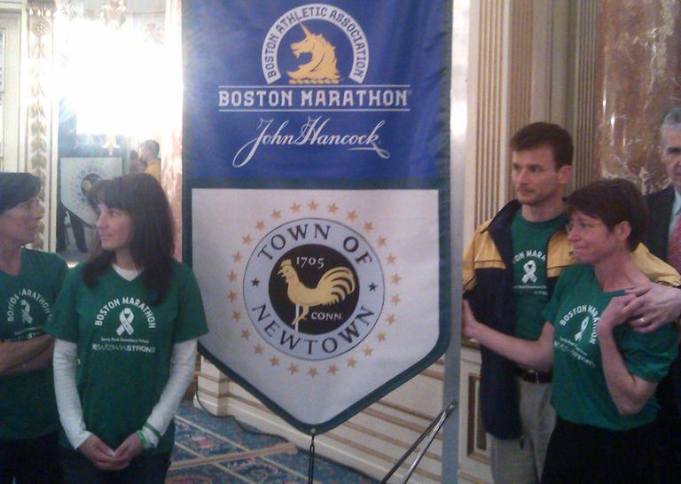 """A group of parents from Newtown, Conn. is running the marathon in memory of the 26 people killed in the mass shooting there in December. Laura Nowacki (far right) says """"We're all parents. We're Sandy Hook parents. We're also runners and we are here to run 26 miles for 26 lives."""" Nowacki's daughter survived the shooting. (Alex Ashlock/Here & Now)"""