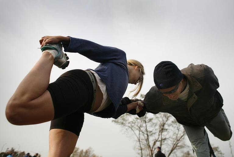 Heather Beaudoin, left, and Greg Motylenski, both of Manhattan, help each other stretch before the start of the New York City Marathon Sunday, Nov. 5, 2006 in New York. (Jason DeCrow/AP)
