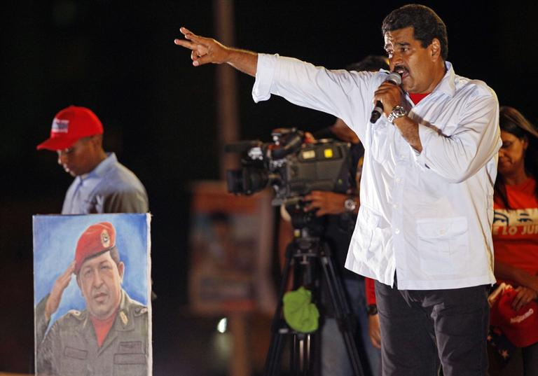 Venezuela's acting President Nicolas Maduro speaks during his closing campaign rally in Caracas, Venezuela, Thursday, April 11, 2013. Maduro, the hand-picked successor of Venezuela's late President Hugo Chavez whose portrait stands at left, is running for president against opposition candidate Henrique Capriles on April 14. (Ramon Espinosa/AP)