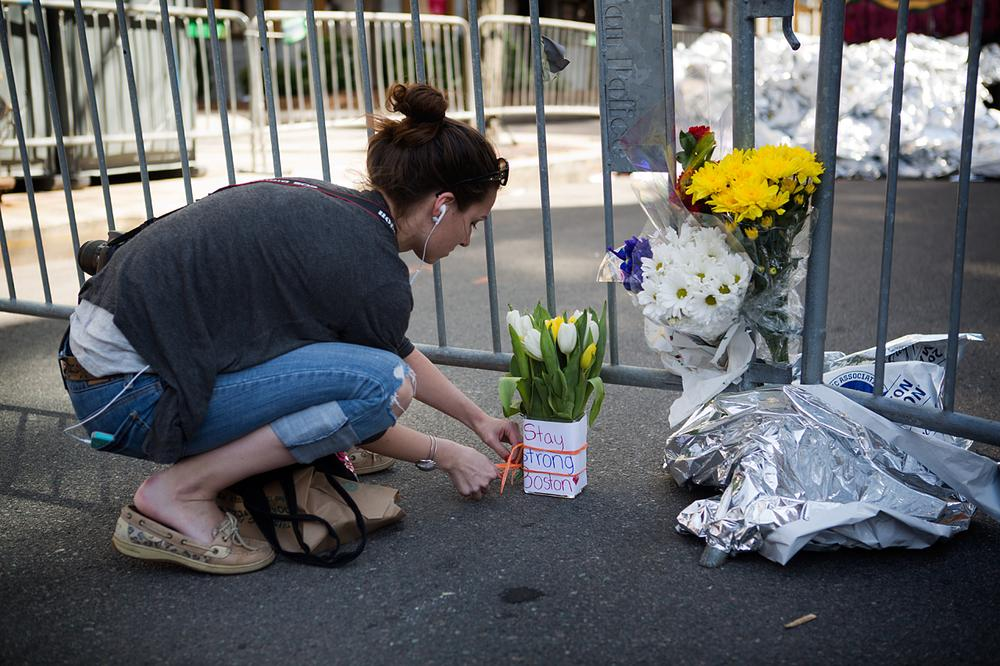 Caitlin Drown of Brewster leaves flowers at a memorial at Clarendon and Newbury Streets. (Jesse Costa/WBUR)