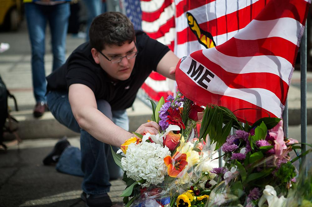 Leif Ruben of Back Bay props up flowers blown over by the wind at the Memorial at Berkeley and Boylston St. (Jesse Costa/WBUR)