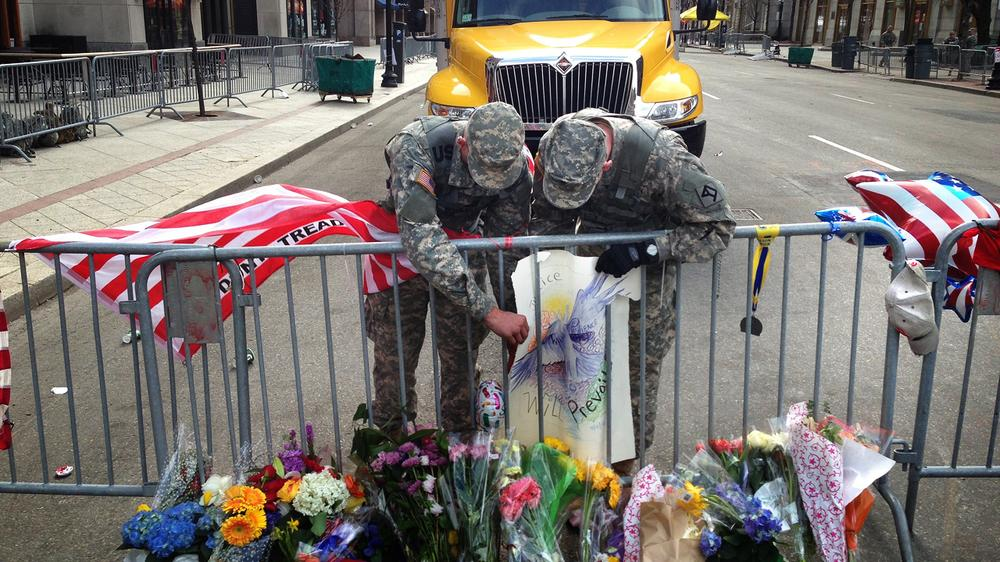 Two Army National Guardsmen adjust a poster that is part of a memorial set up on Berkeley Street. (Jesse Costa/WBUR)