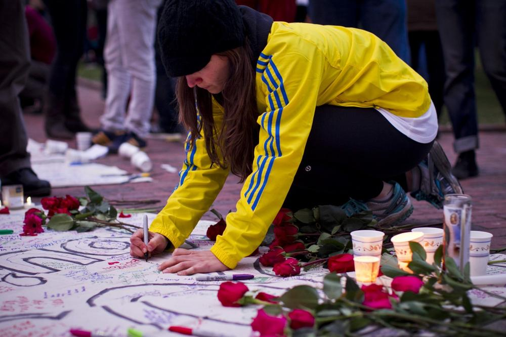 Amanda Ayers leaves a note on a banner during a candlelight vigil at the Boston Common on Tuesday evening, April 16, 2013, a day after two explosions near the Boston Marathon finish line killed three people and injured more than 140 participants and spectators. (Dominick Reuter for WBUR)