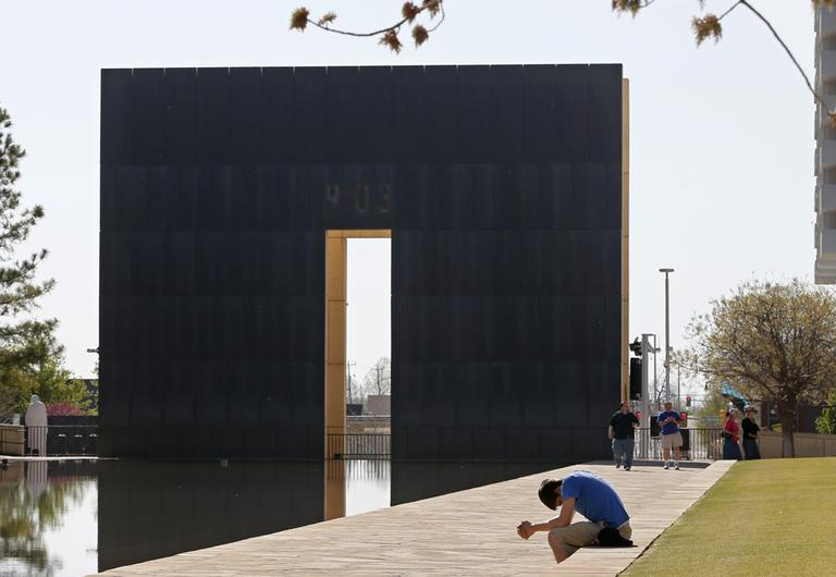 Shane Magness, a student at Oklahoma Christian University, bows his head in prayer for the victims of the Boston Marathon bombing, at the Oklahoma City National Memorial in Oklahoma City, Monday, April 15, 2013. (Sue Ogrocki/AP)