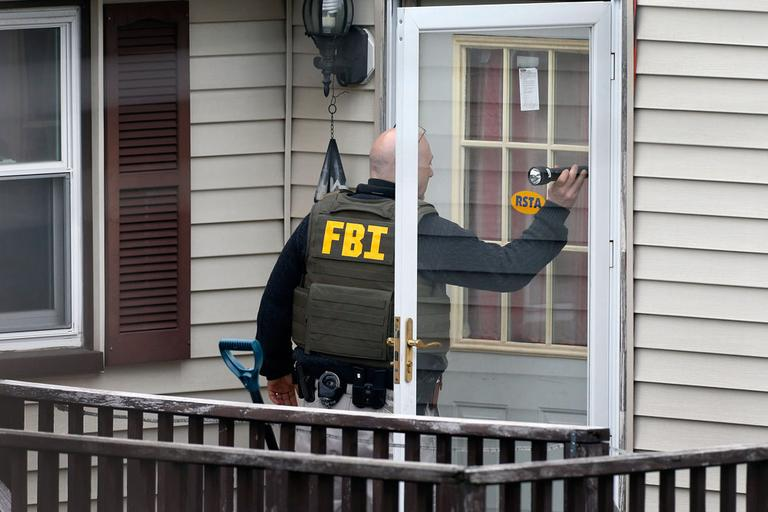 An FBI agent goes door-to-door evacuating residents of Norfolk Street as investigators search for a suspect in the Boston Marathon bombings, in Cambridge, Mass., Friday, April 19, 2013.(AP Photo/Michael Dwyer)