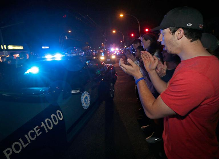 A man applauds as police leave the Watertown scene of the arrest of a suspect of the Boston Marathon bombings Friday night. (Charles Krupa/AP)