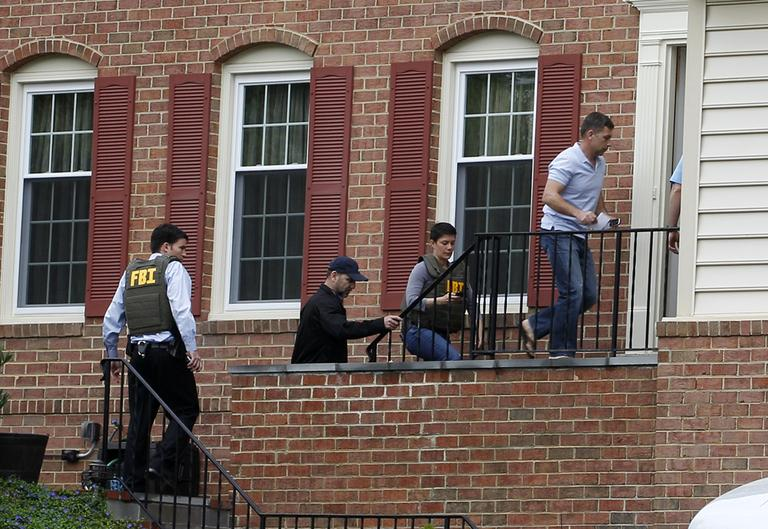 FBI agents escort Ruslan Tsarni, uncle of the Boston Marathon bombing suspects, second from right, into his home in Montgomery Village in Md. Friday, April, 19, 2013. (Jose Luis Magana/AP)