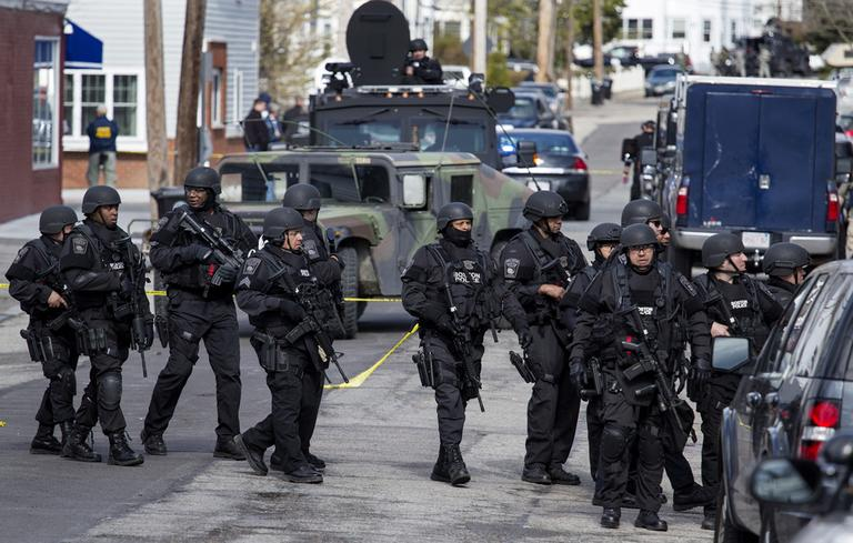Heavily armed police patrol the neighborhoods of Watertown, Mass. Friday, April 19, 2013, as they continue a massive search for one of two suspects in the Boston Marathon bombing. (Craig Ruttle/AP)