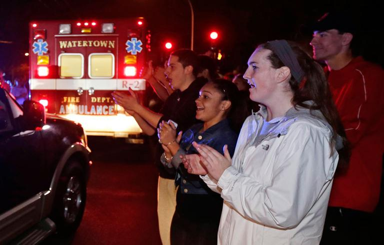 A gathering of people applaud as first responders leave the scene after the arrest of a suspect of the Boston Marathon bombings in Watertown, Mass., Friday, April 19, 2013. (AP Photo/Charles Krupa)