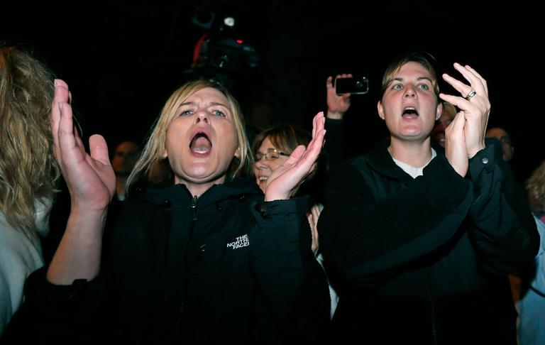 Two women applaud after the arrest of a suspect of the Boston Marathon bombings in Watertown, Mass., Friday, April 19, 2013. (AP Photo/Charles Krupa)