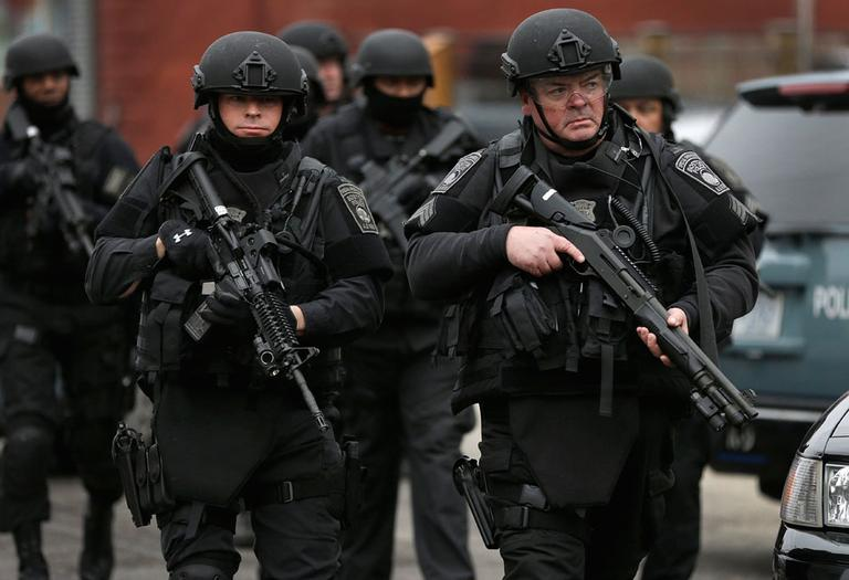 Police in tactical gear conduct a search for a suspect in the Boston Marathon bombings, Friday, April 19, 2013, in Watertown, Mass. (AP Photo/Matt Rourke)