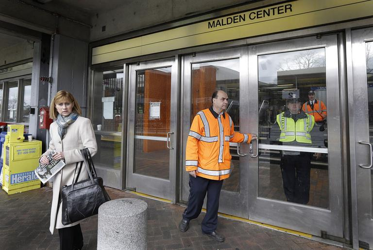 MBTA transit police turn away a commuter at Malden Center station in Malden, Mass. Friday, April 18, 2013 as area MBTA commuter trains are suspended. (Elise Amendola/AP)