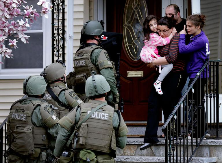 A woman carries a girl from their home as a SWAT team searching for a suspect in the Boston Marathon bombings enters the building in Watertown, Mass., Friday, April 19, 2013. (AP Photo/Charles Krupa)