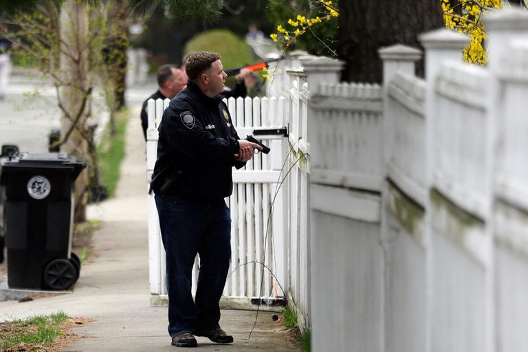 A police officer with is weapon drawn conducts a search for a suspect in the Boston Marathon bombings, Friday, April 19, 2013, in Watertown, Mass. (AP Photo/Matt Rourke)