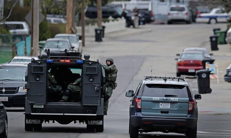 A SWAT team drives through a neighborhood while searching for a suspect in the Boston Marathon bombings in Watertown, Mass., Friday, April 19, 2013. (AP Photo/Charles Krupa)