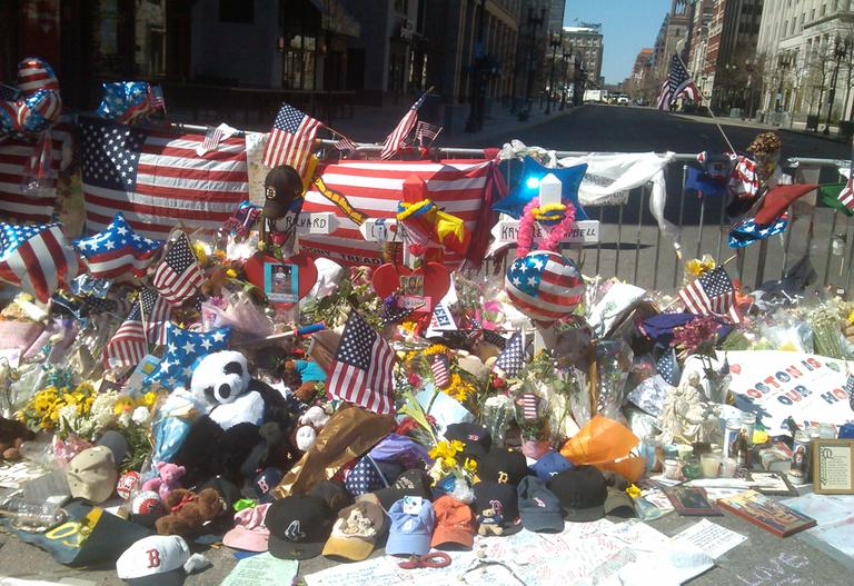 A makeshift memorial near the finish line of the Boston Marathon is pictured on Sunday, April 21. (Alex Ashlock/Here & Now)