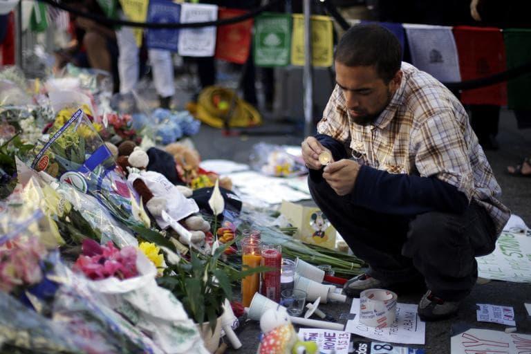 Richard Maldonado lights a candle at a makeshift memorial on Boylston Street near the finish line of the Boston Marathon explosions. (Matt Rourke/AP)