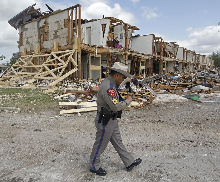 Texas Department of Public Safety Sgt. Jason Reyes walks past a damaged apartment complex, Sunday, April 21, 2013, four days after an explosion at a fertilizer plant in West, Texas. (Michael Ainsworth/The Dallas Morning News/AP)