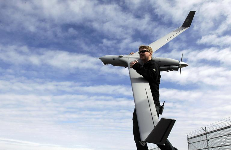 This photo taken March 26, 2013, shows flight test pilot Alex Gustafson carrying an InsituScanEagle unmanned aircraft in preparation for a flight in Arlington, Ore. It's a good bet that in the not-so-distant future aerial drones will be part of Americans' everyday lives, performing countless useful functions. (Don Ryan/AP)