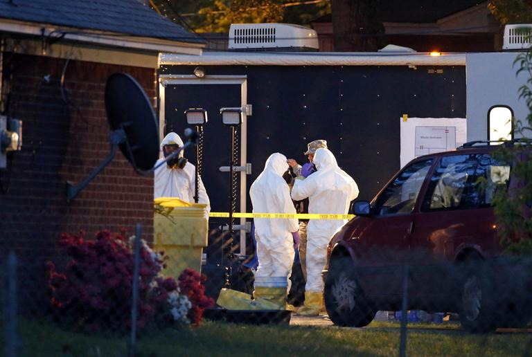 Federal authorities wear hazmat suits as they search the home of Everett Dutschke, Tuesday, April 23, 2013 in Tupelo, Miss., in connection with the recent ricin attacks. (Rogelio V. Solis/AP)