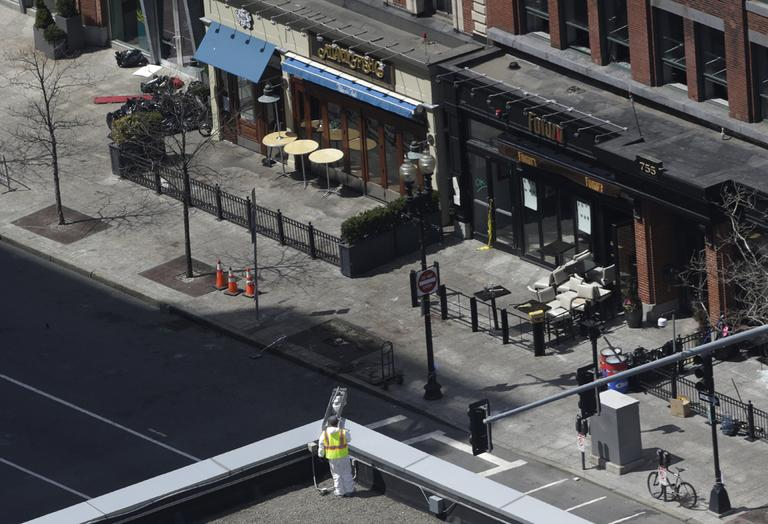 An investigator inspects the area around a surveillance camera near the Boston Marathon finish line that an official says is crucial in the investigation of the bombings, Thursday, April 18, 2013. (Julio Cortez/AP)