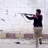 This image taken from video shows free Syrian Army fighters firing at Syrian army soldiers during a fierce firefight in Daraa al-Balad, Syria, March 18, 2013. (Shaam News Network via AP)