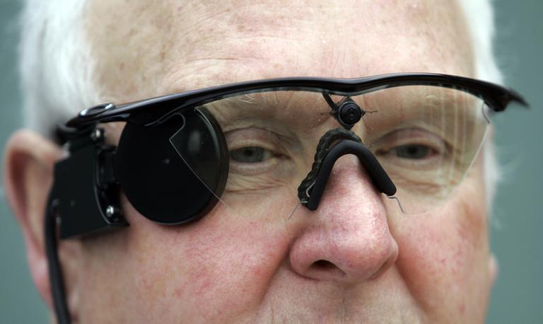 "Eric Selby poses for a photograph in Coventry, England, in February 2011. He's wearing a ""sight"" camera fitted in a pair of glasses, which works in conjunction with an artificial retina implant called the Argus II fitted in his right eye, enabling him to detect light. (Martin Cleaver/AP)"