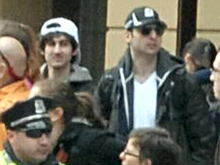 """The FBI released this image early Friday, April 19, 2013, showing """"Suspect 1"""" in the white cap and """"Suspect 2"""" in the black cap, walking through the crowd in Boston on Monday, April 15, 2013, before the explosions at the Boston Marathon. (FBI/AP)"""